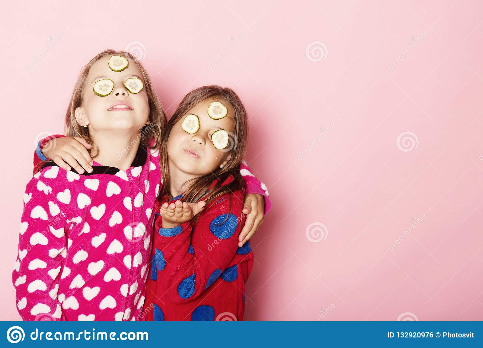Girls in bright pink pajamas hug. Kids on pink background