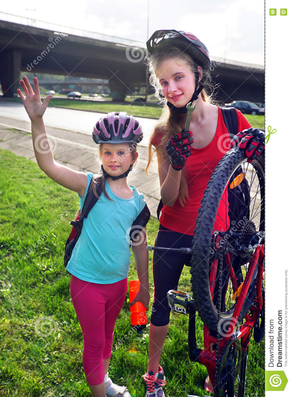 Girls children cycling pump up bicycle tire.