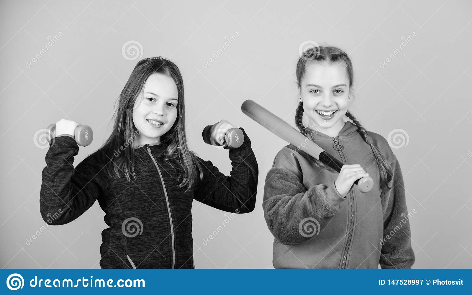Girls cute kids with sport equipment dumbbells and baseball bat. We love sport. Child might excel in completely