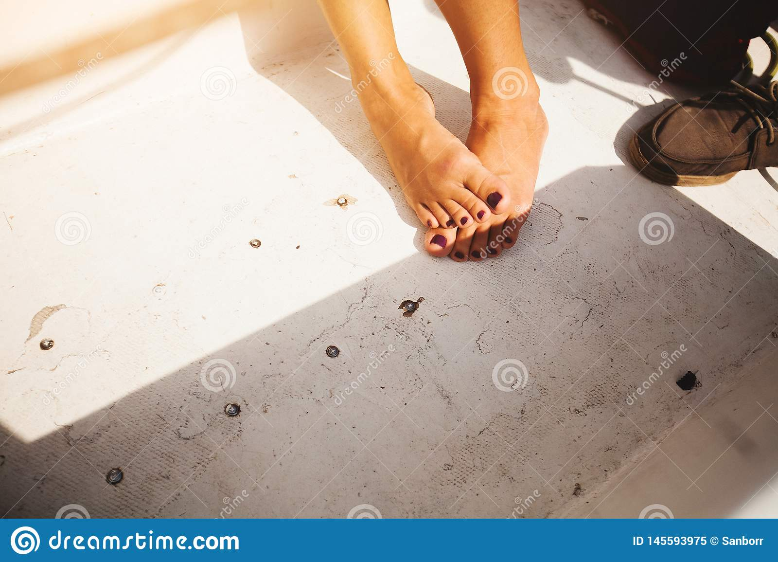 Girls feet without shoes with a pretty pedicure in the sunlight on the bright background of the old floor. The concept of a summer