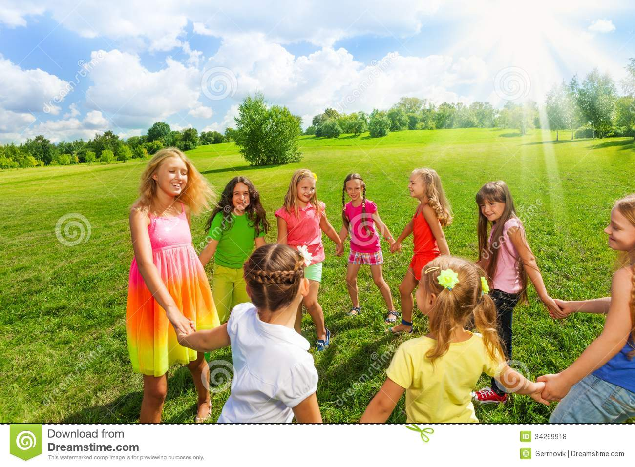 Large group of girls play roundelay and stand in circle in the park on