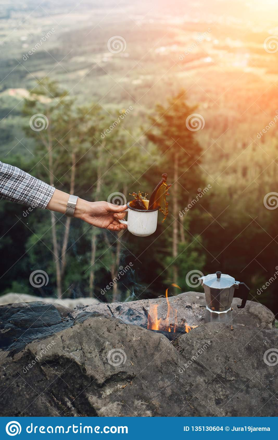 Girls hand holds a hot cup of coffee near the campfire on background of nature during the sunset