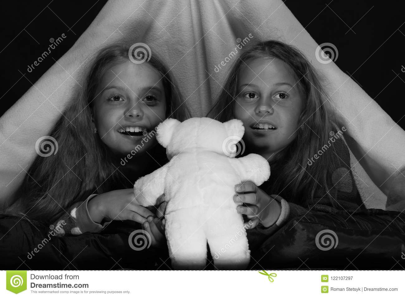 Girls with happy faces watching TV. Kids wearing red jammies in bed on black  background. Friends having fun with toys in blanket tent. 370daadf4