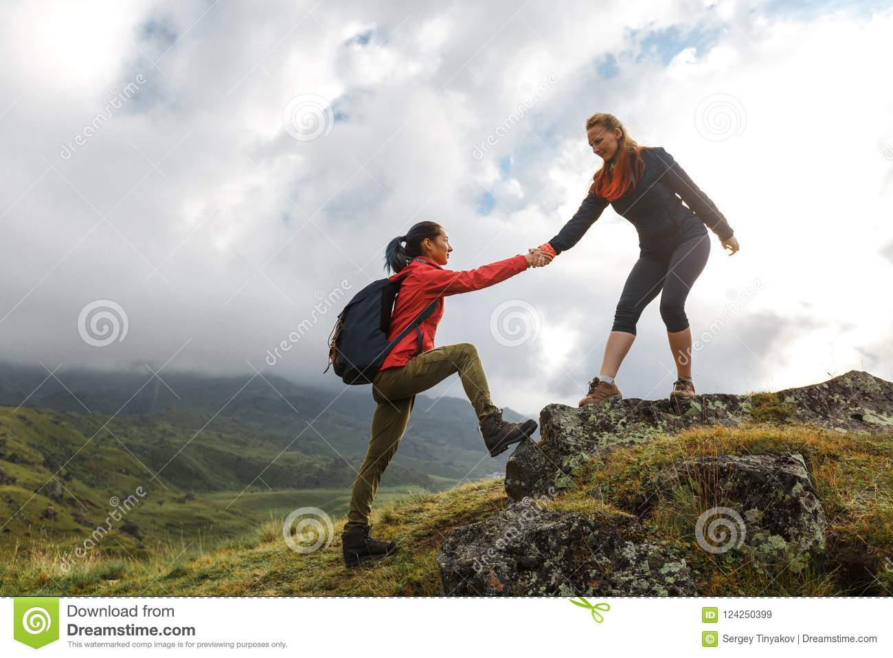 Girls helping each other hike up a mountain at sunrise. Giving a