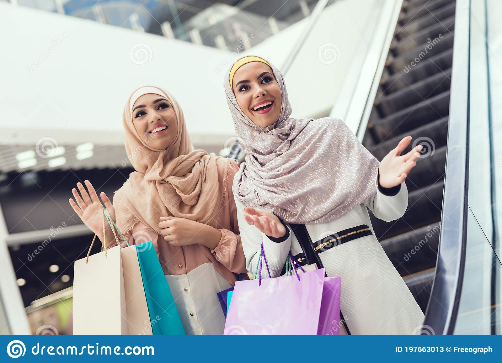 Young Arabian Women With Packages Standing In Mall Stock