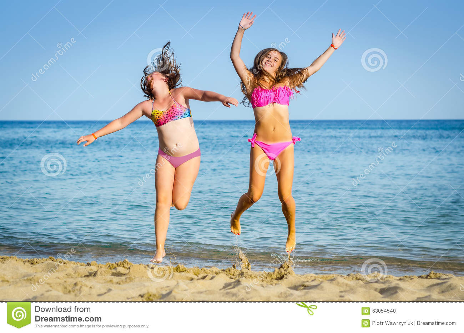 2dd42ac138e25 Girls Jumping On Tropical Beach Stock Photo - Image of having ...