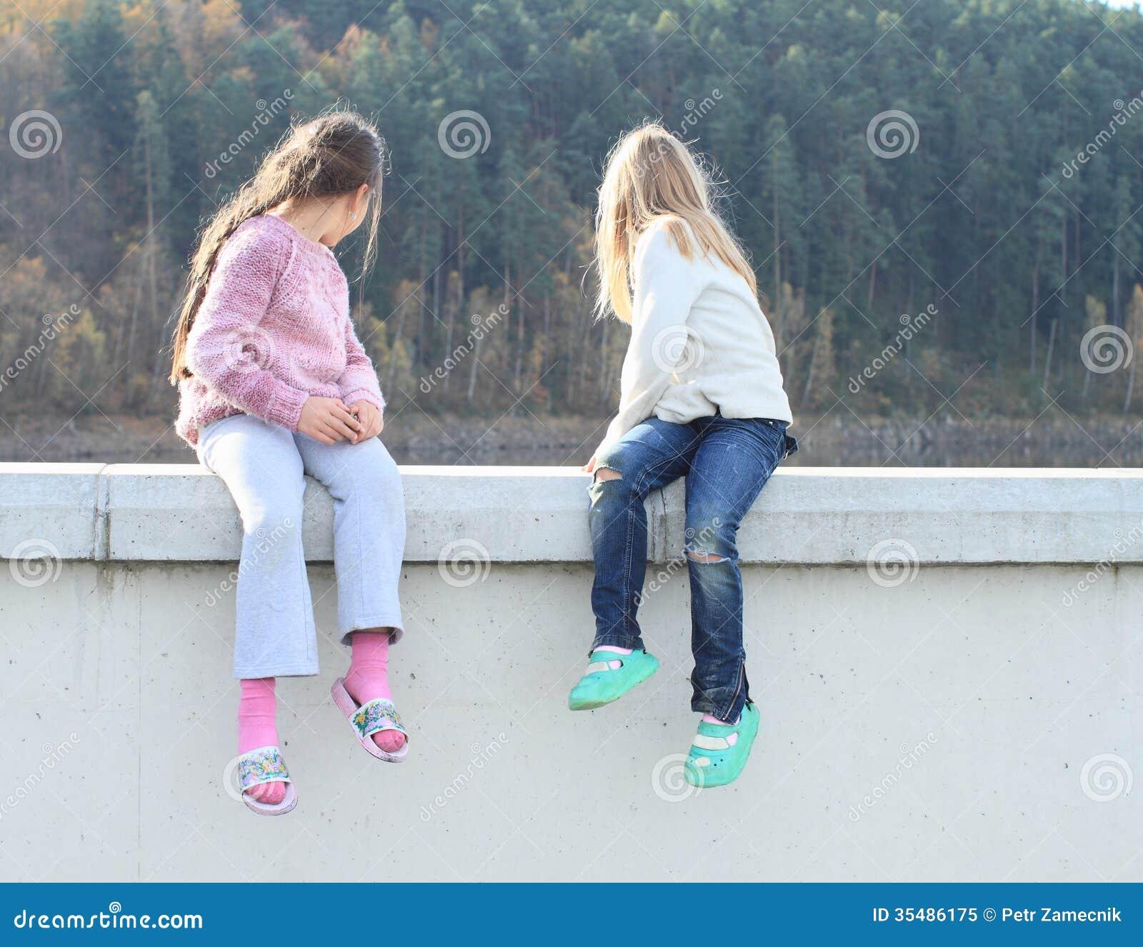 girls looking behind wall royalty free stock photo