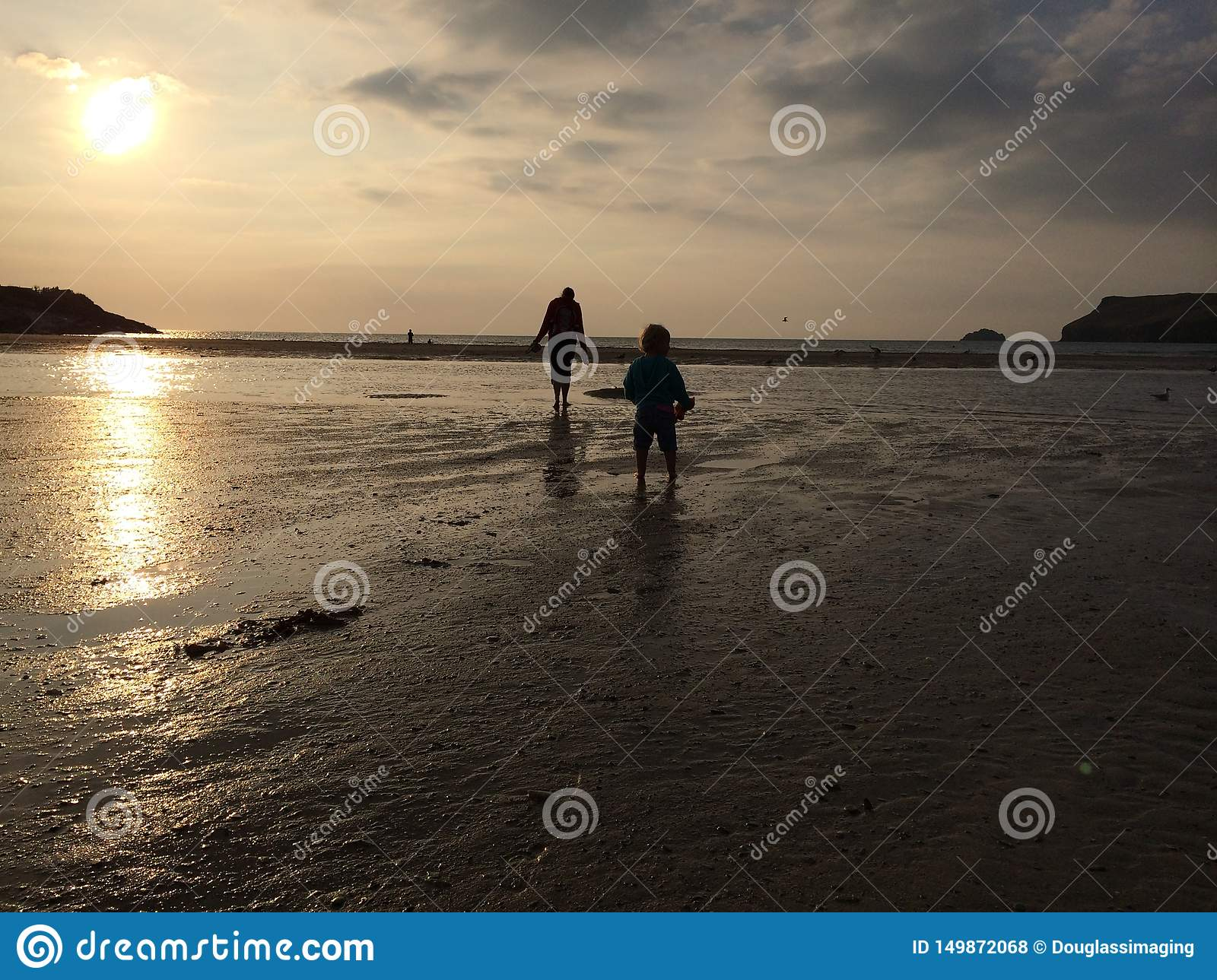 Girls and mother walking on sunset beach
