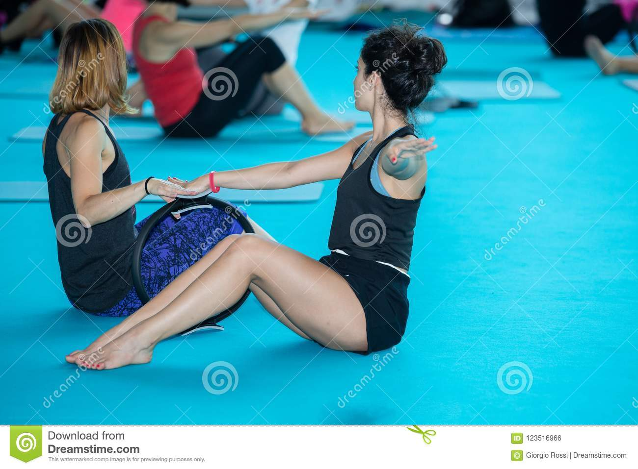 Girls with Outstretched Arms doing Fitness Exercises on Mat at Gym