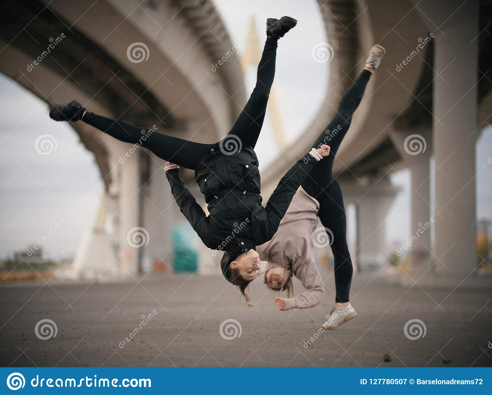 Girls perform splits in the air while jumping on the urban background of the bridge