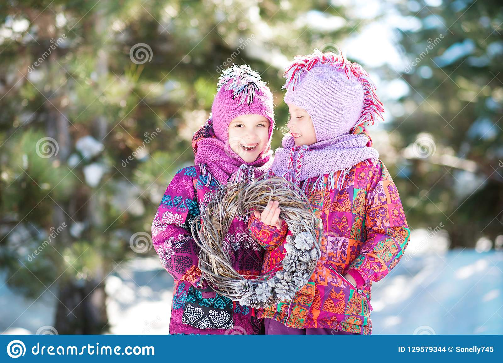 Girls in pink suits hold a Christmas wreath in winter. Children`s winter holidays