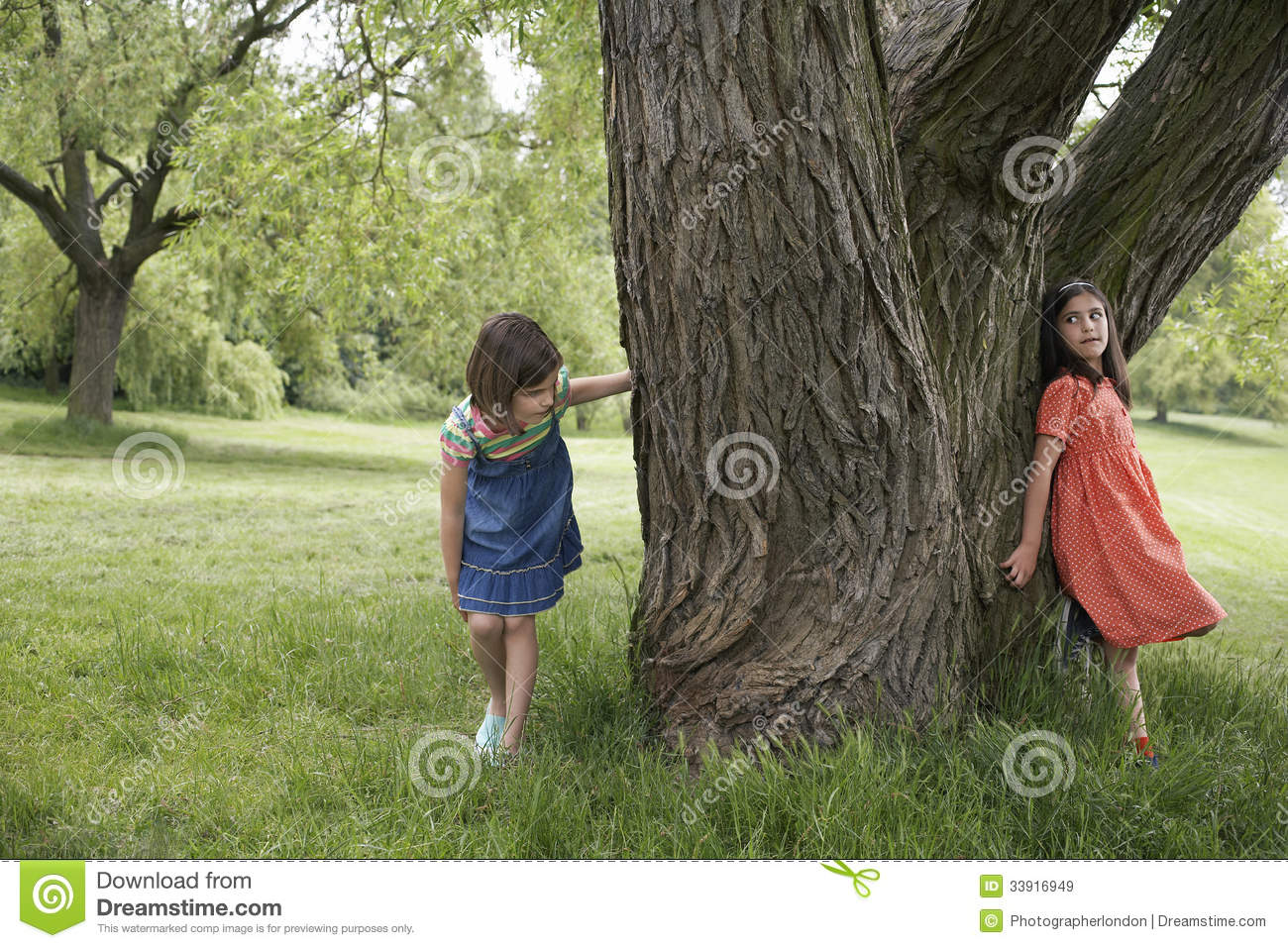 girls playing hide and seek by tree stock image image of childhood park 33916949. Black Bedroom Furniture Sets. Home Design Ideas