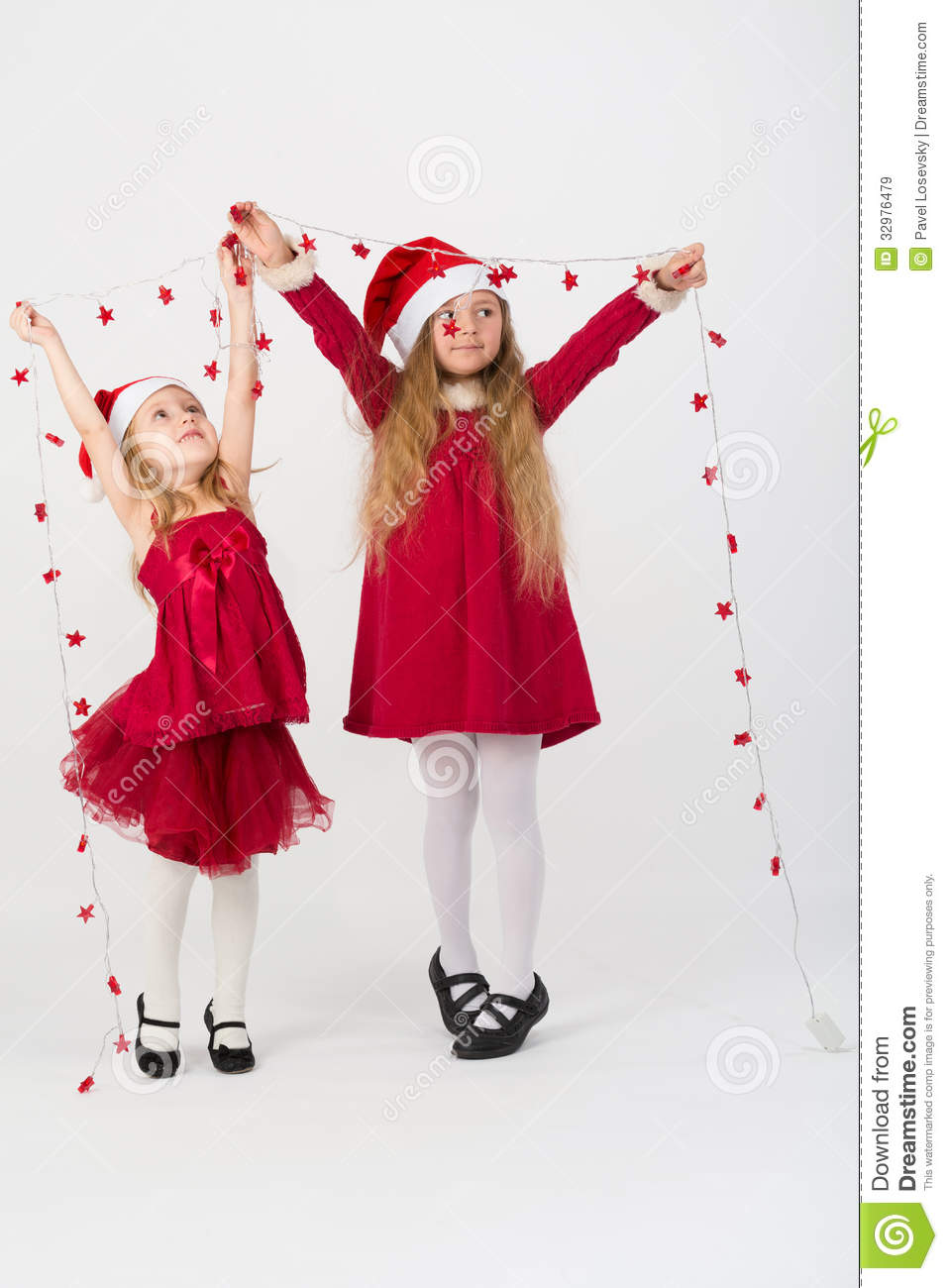 Girls in a red dress caps santa claus holding garland