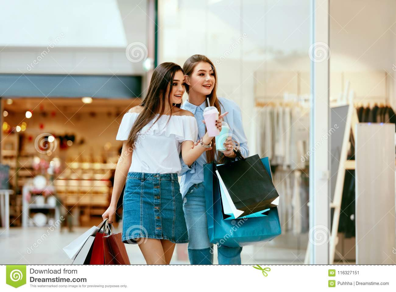 689ee6993 Girls Shopping. Beautiful Happy Female Friends With Colorful Bags Walking  In Mall. High Resolution.