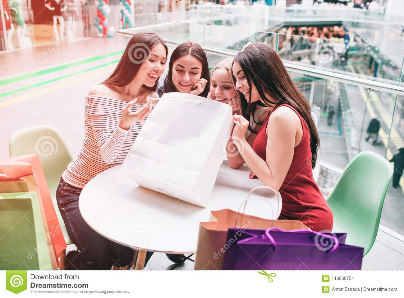 Girls are sitting at the table and looking into shopping bag. They are happy and very excited.