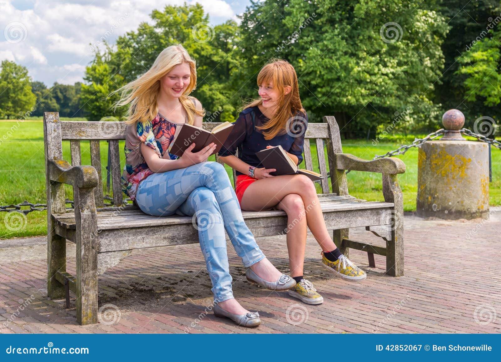 Girls Sitting On Wooden Bench In Park Reading Books Stock