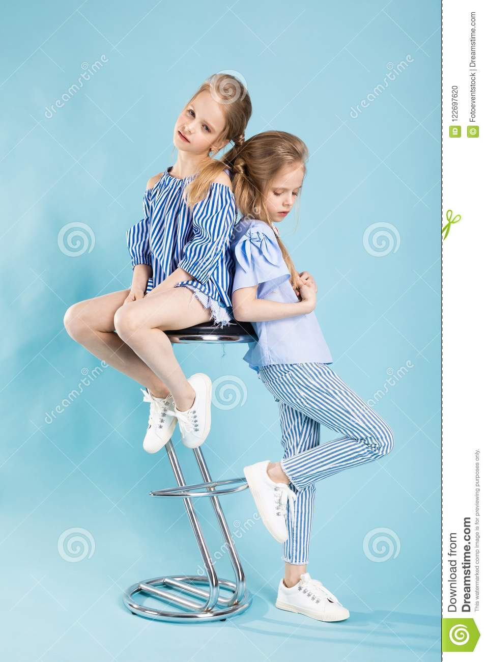 229e305de Girls Twins In Light Blue Clothes Are Posing Near A Bar Stool On A ...
