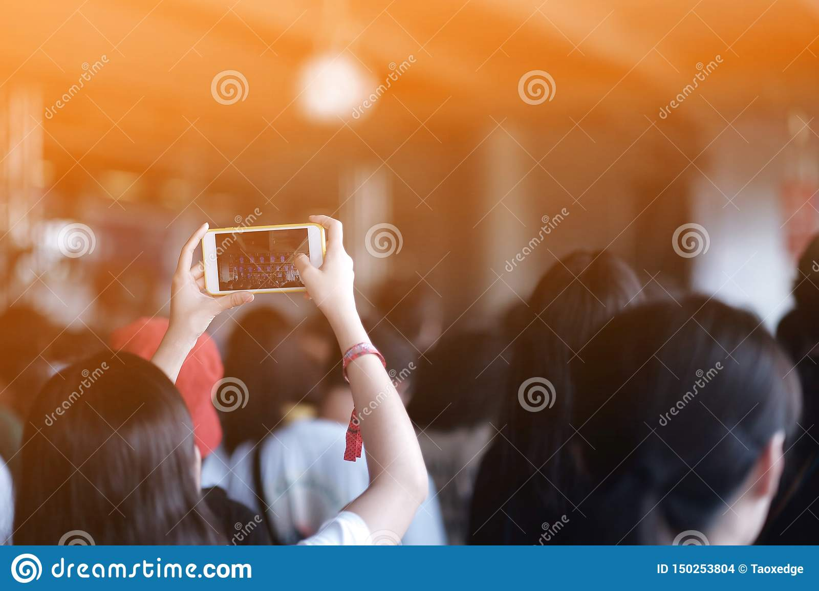 Girls use smartphones to take pictures at concerts