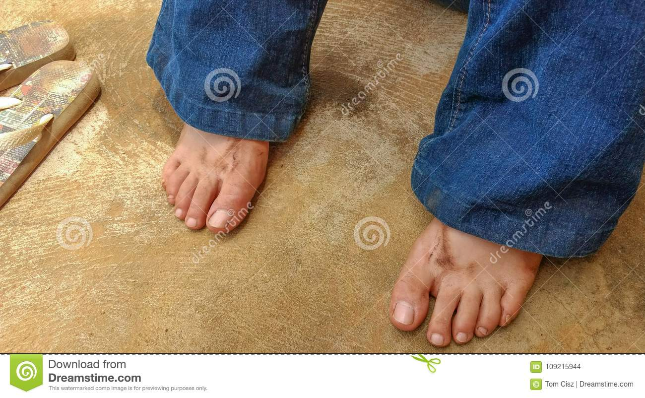 6b205b5865e8 Royalty-Free Stock Photo. Dirty girl`s feet resting with flip-flops next to  her after working in