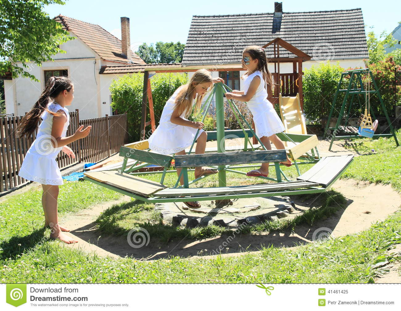 Girls in white dresses on marry-go-round