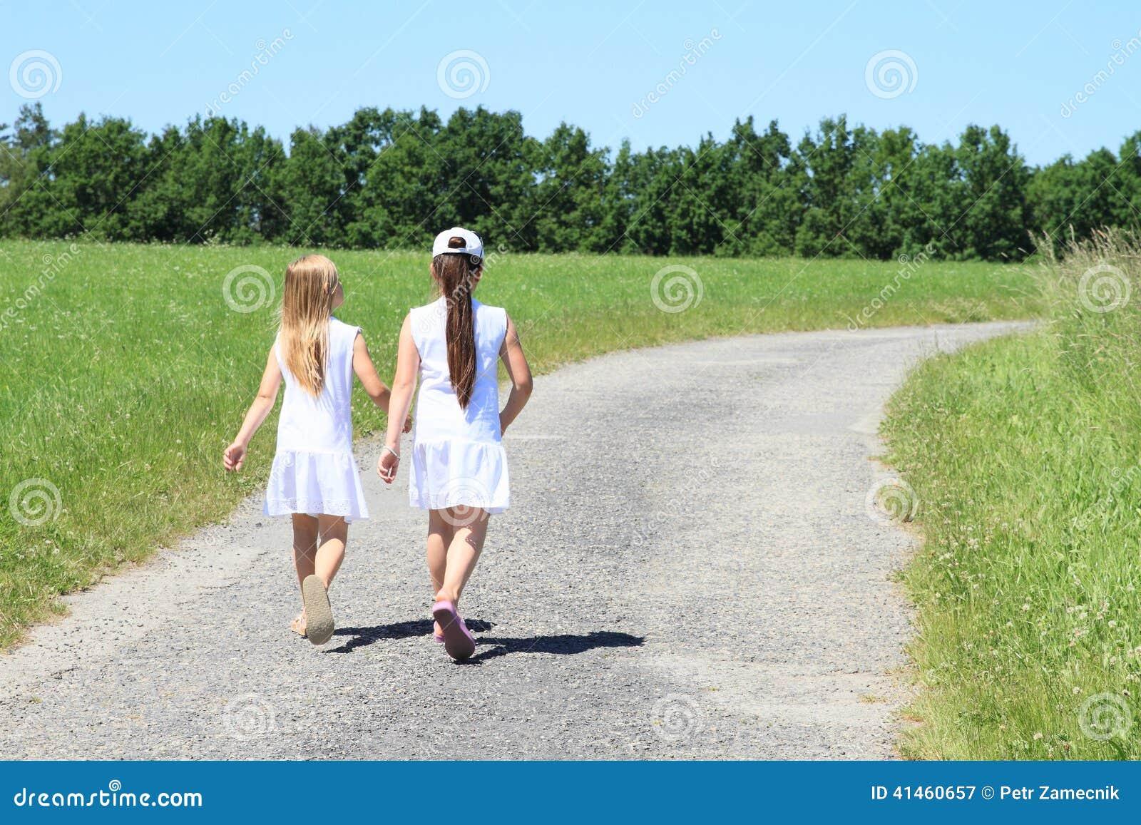 Girls in white dresses on road