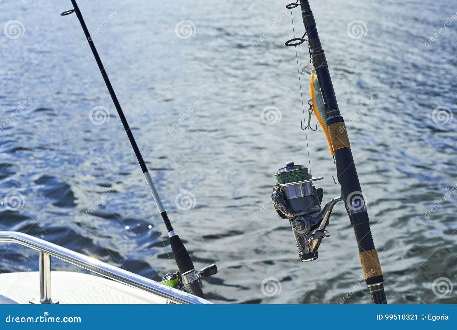 Giro con la pesca con cebo de cuchara con cebo de cuchara en el casco del ` s de la nave contra el fondo