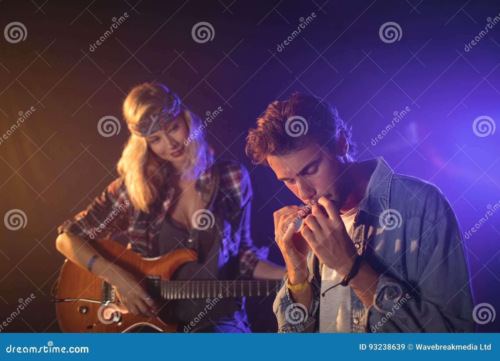 Gitarist die musicus het spelen harmonika in muziekoverleg bekijken
