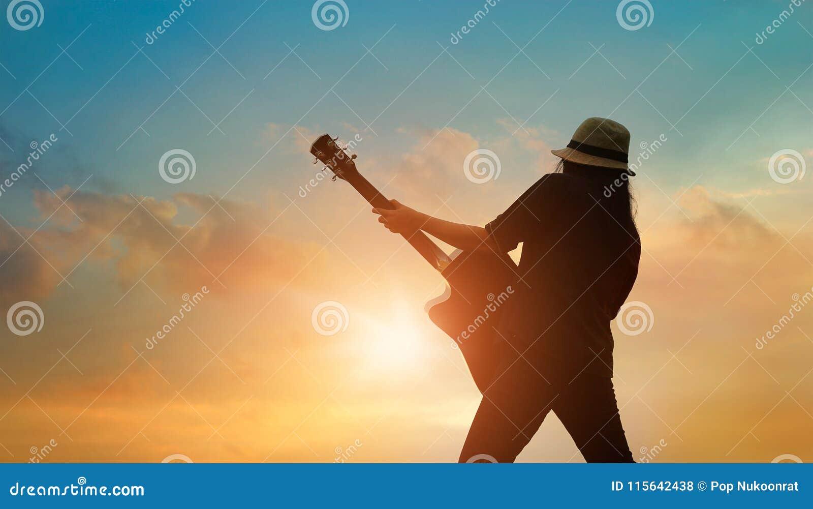 Gitarrist som spelar den akustiska gitarren på den färgrika cloudscapesolnedgången