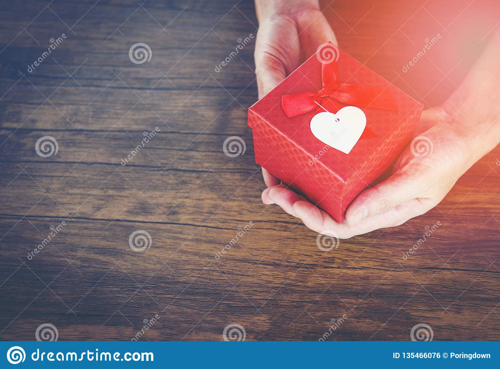 Give Love Man holding small red present box in hands with Heart for love Valentines day Giving a gift box with red ribbon