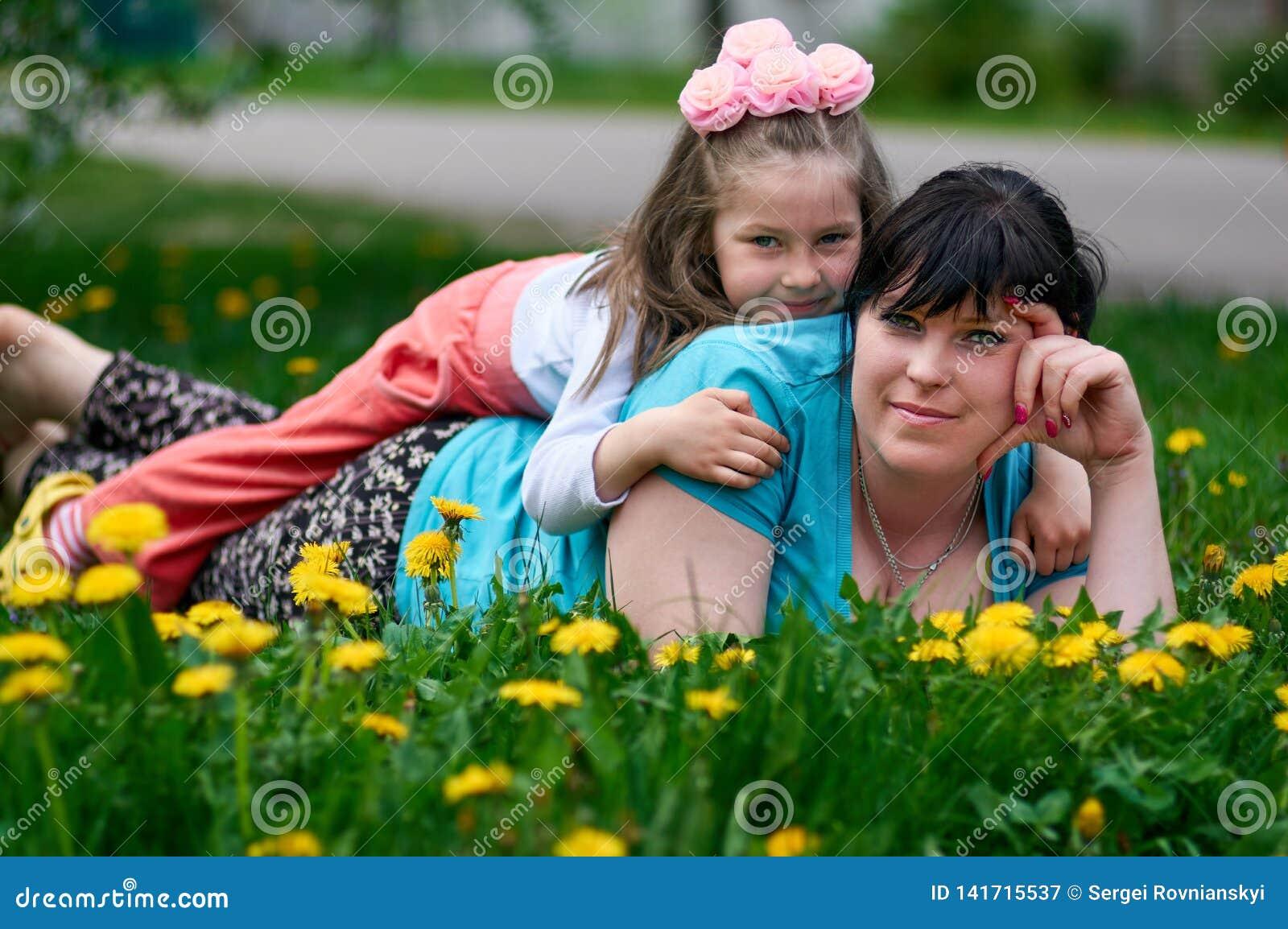 Glückliche junge Mutter mit Baby genießt Sommerzeit in einer Löwenzahnwiese