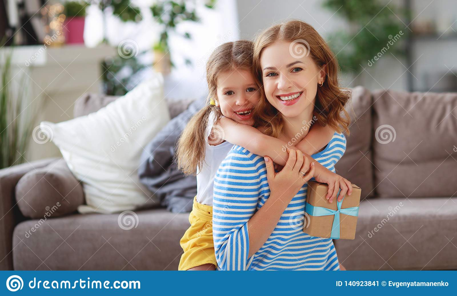Glücklicher Muttertag! Kindertochter gibt Mutter einen Blumenstrauß von Blumen zur Tulpe und zum Geschenk
