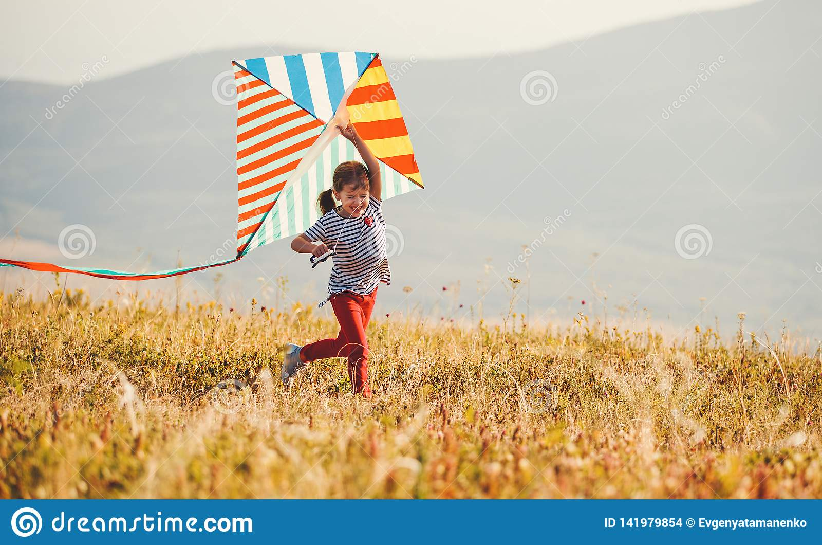 Glückliches Kindermädchen, das draußen mit Drachen bei Sonnenuntergang läuft