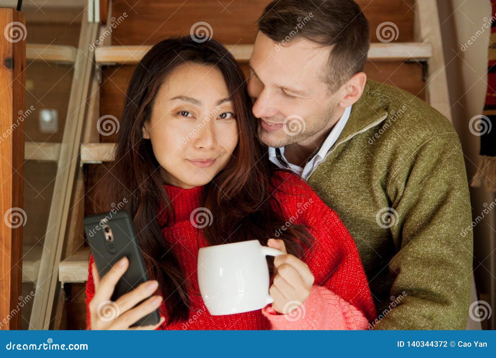 Glückliches Paar sitzen auf dem Treppenhintergrund der neuen Wohnung