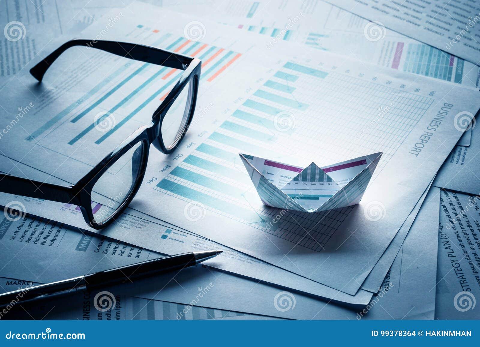 Gläser und Stift mit den Booten hergestellt vom Papierdiagramm