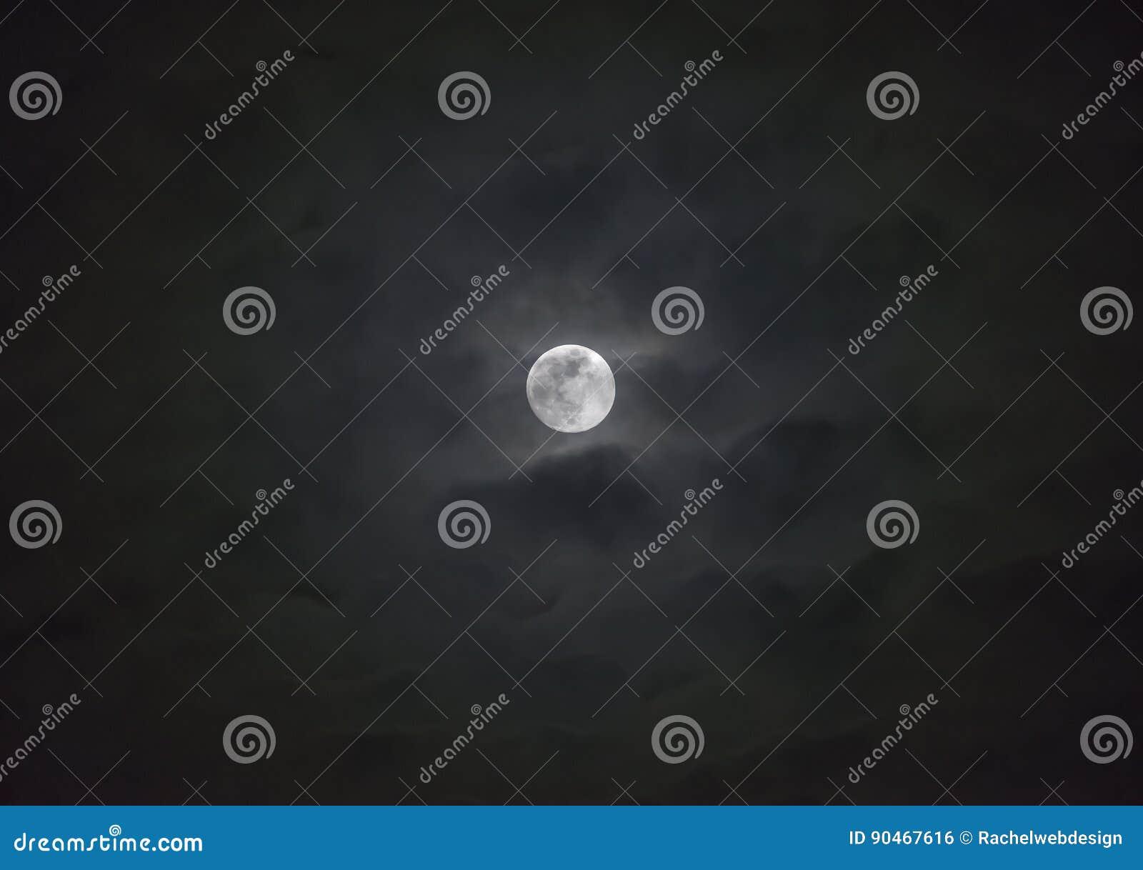 Glödande fullmåne bak wispy lager av lynniga moln, atmosfär