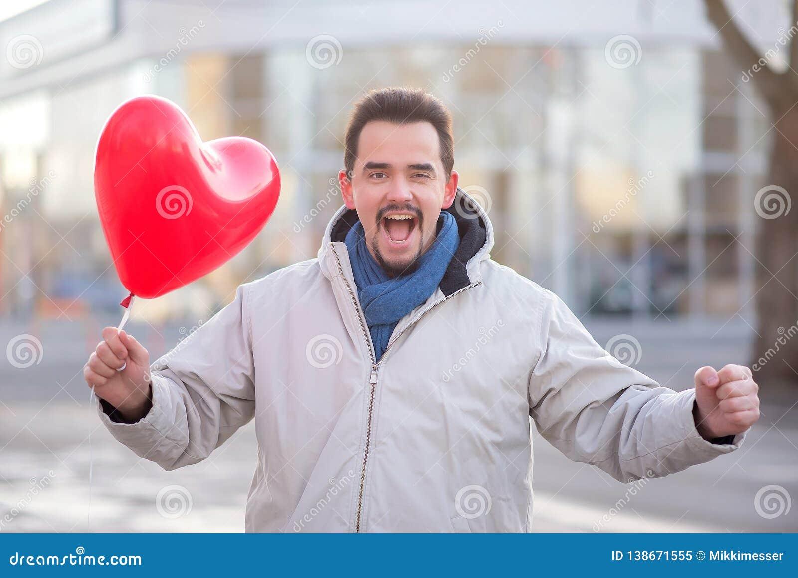 Glücklich lachender gut aussehender Mann mit einer Ballonstellung Luft des roten Herzens geformten in einer Stadtstraße