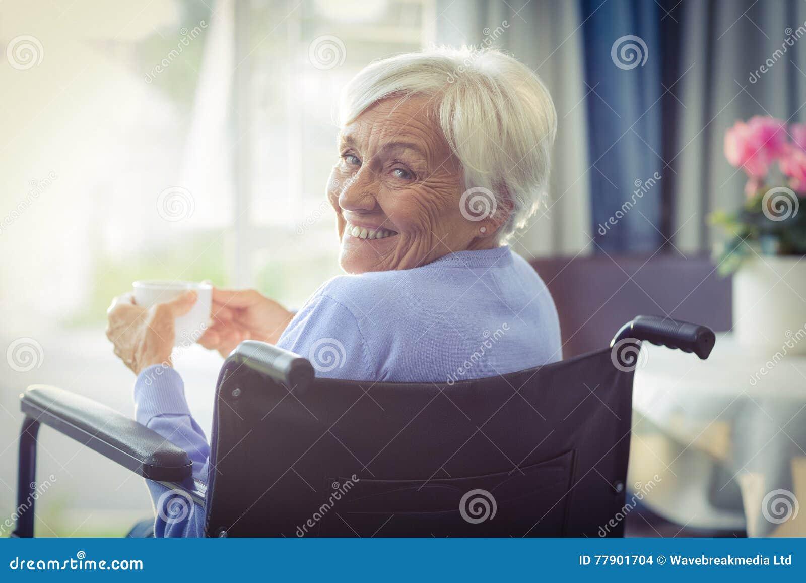 Glückliche ältere Frau auf dem Rollstuhl, der eine Tasse Tee hält