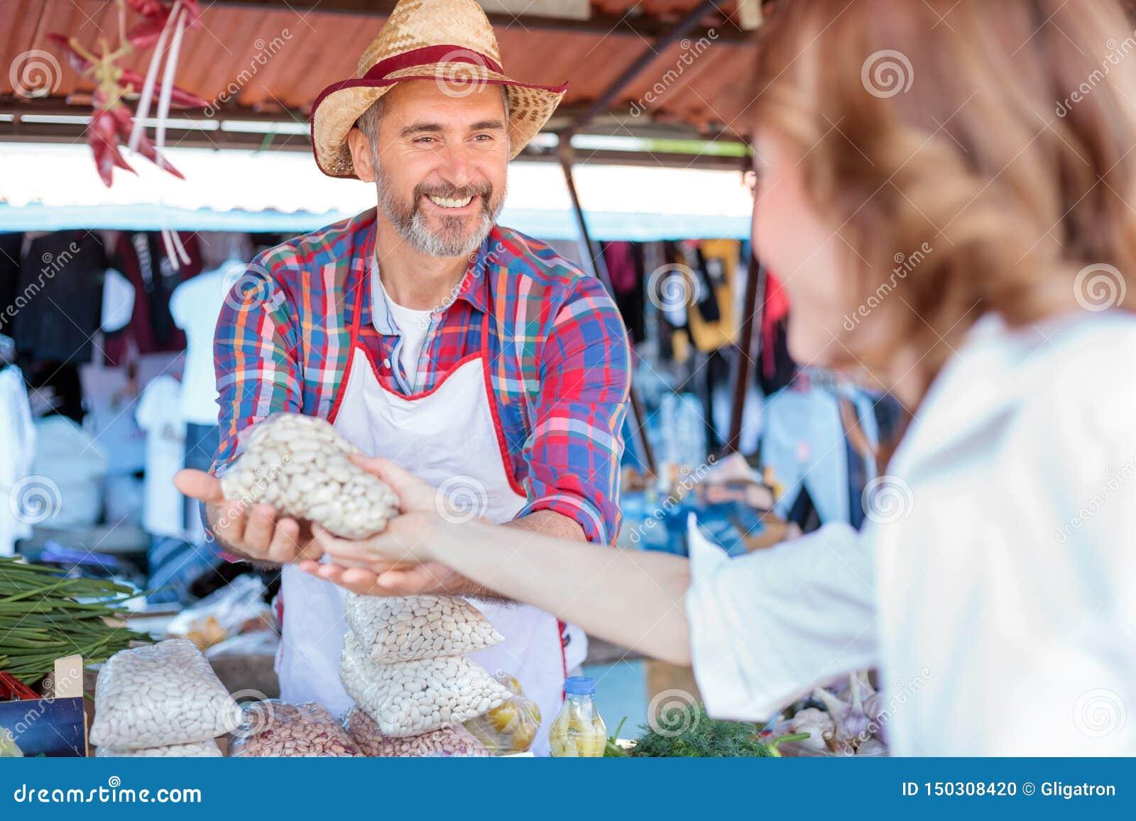 Glückliche ältere Landwirtstellung hinter dem Marktstall, organisches Gemüse verkaufend