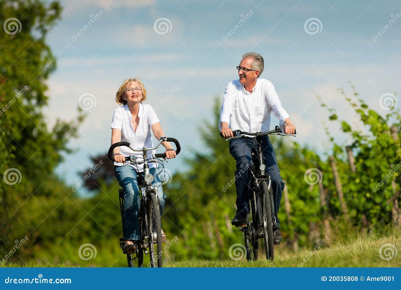 Glückliche ältere Paare, die draußen am Sommer einen Kreislauf durchmachen
