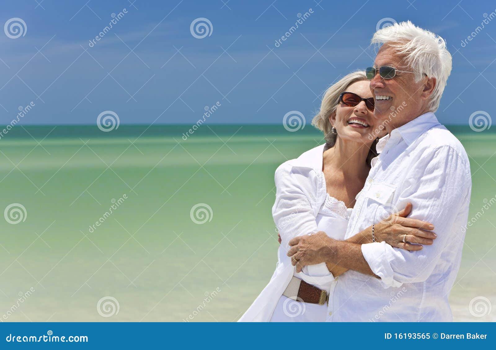 Glückliche ältere Paare, die zum Meer auf Strand schauen