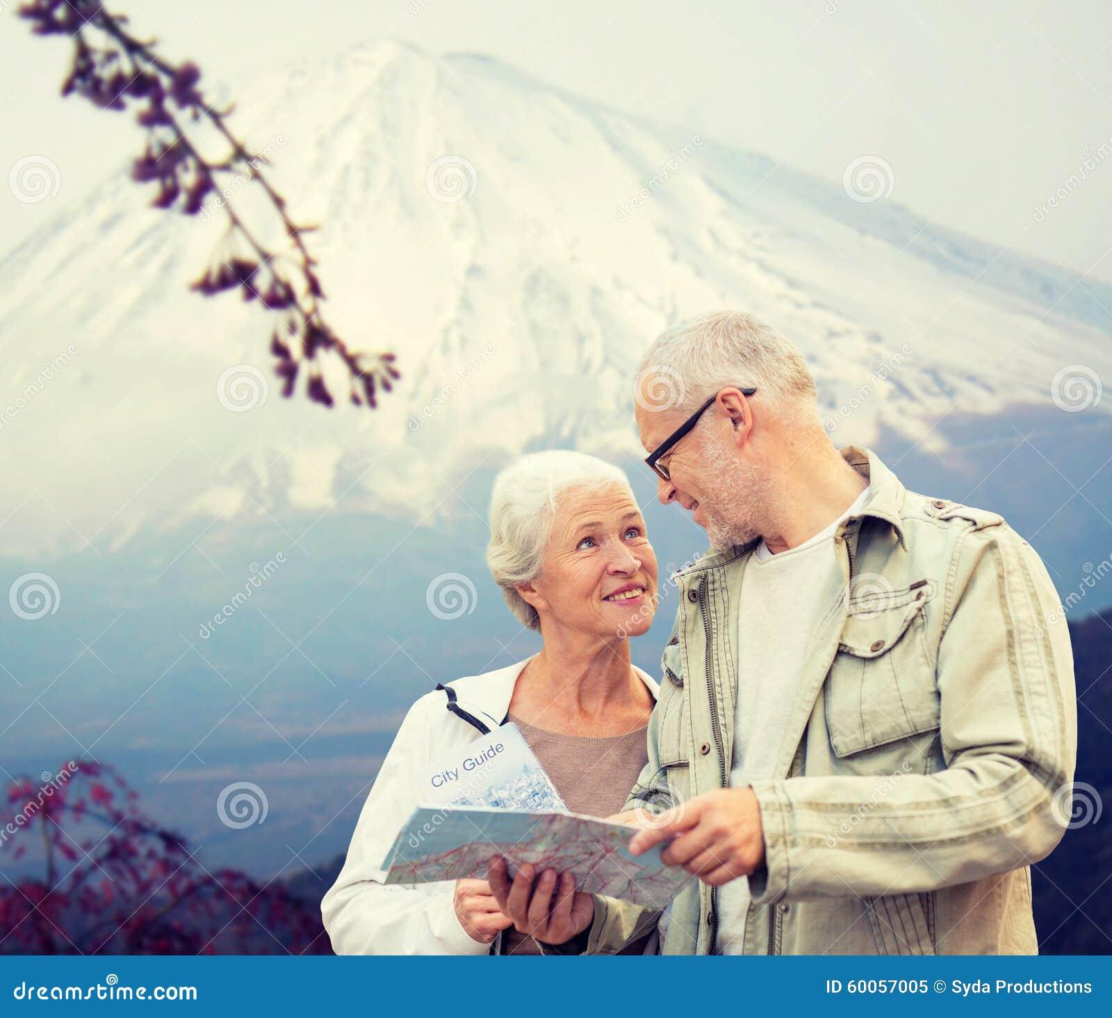 Glückliche ältere Paare mit Reise zeichnen über Bergen auf