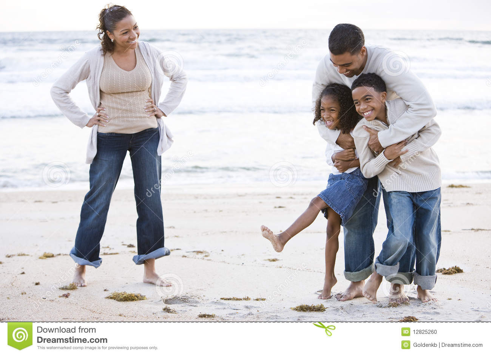 Glückliche African-Americanfamilie, die auf Strand lacht