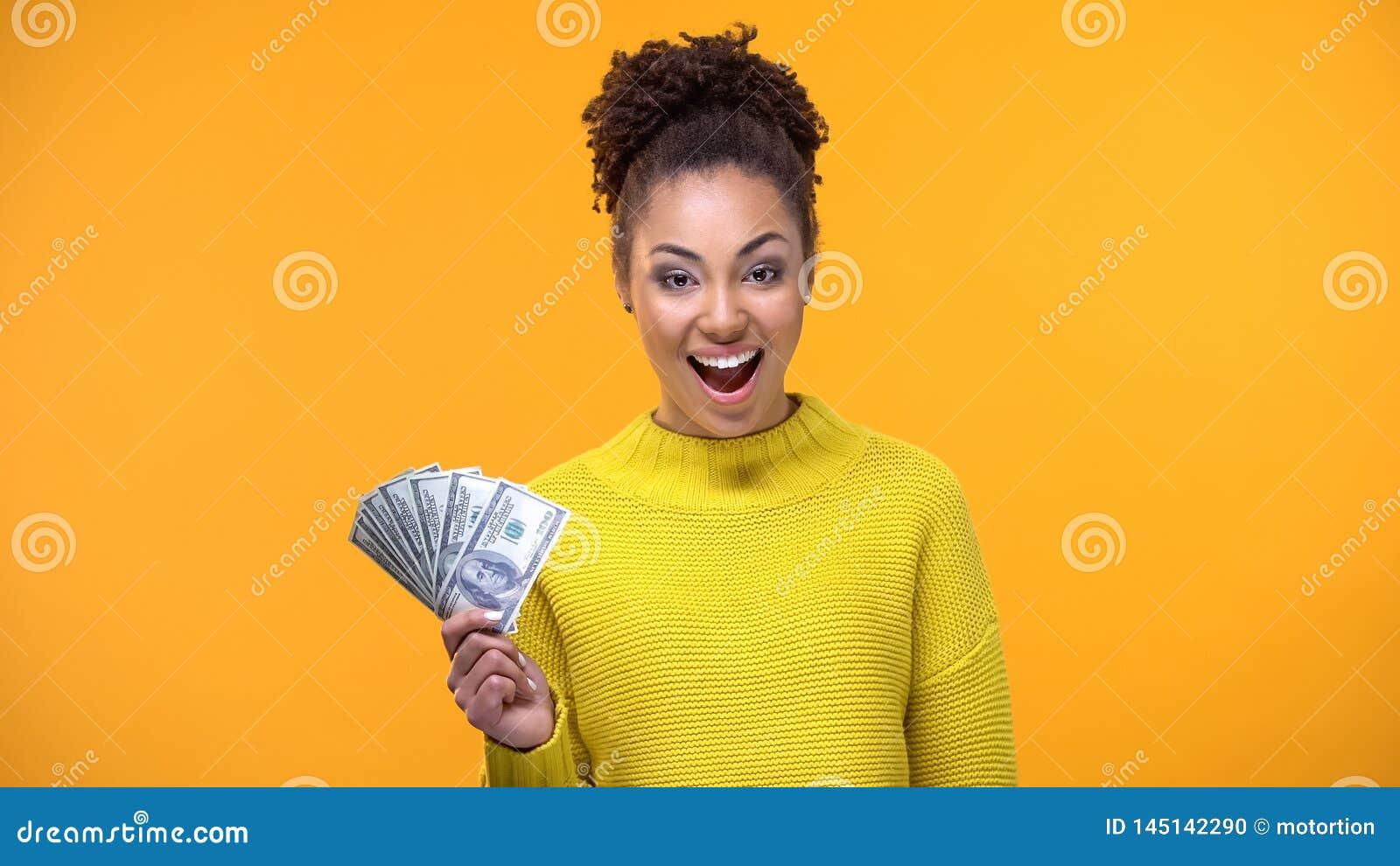 Glückliche afro-amerikanische Dame, die Bündel Dollar auf Kamera, hoch bezahlter Job zeigt