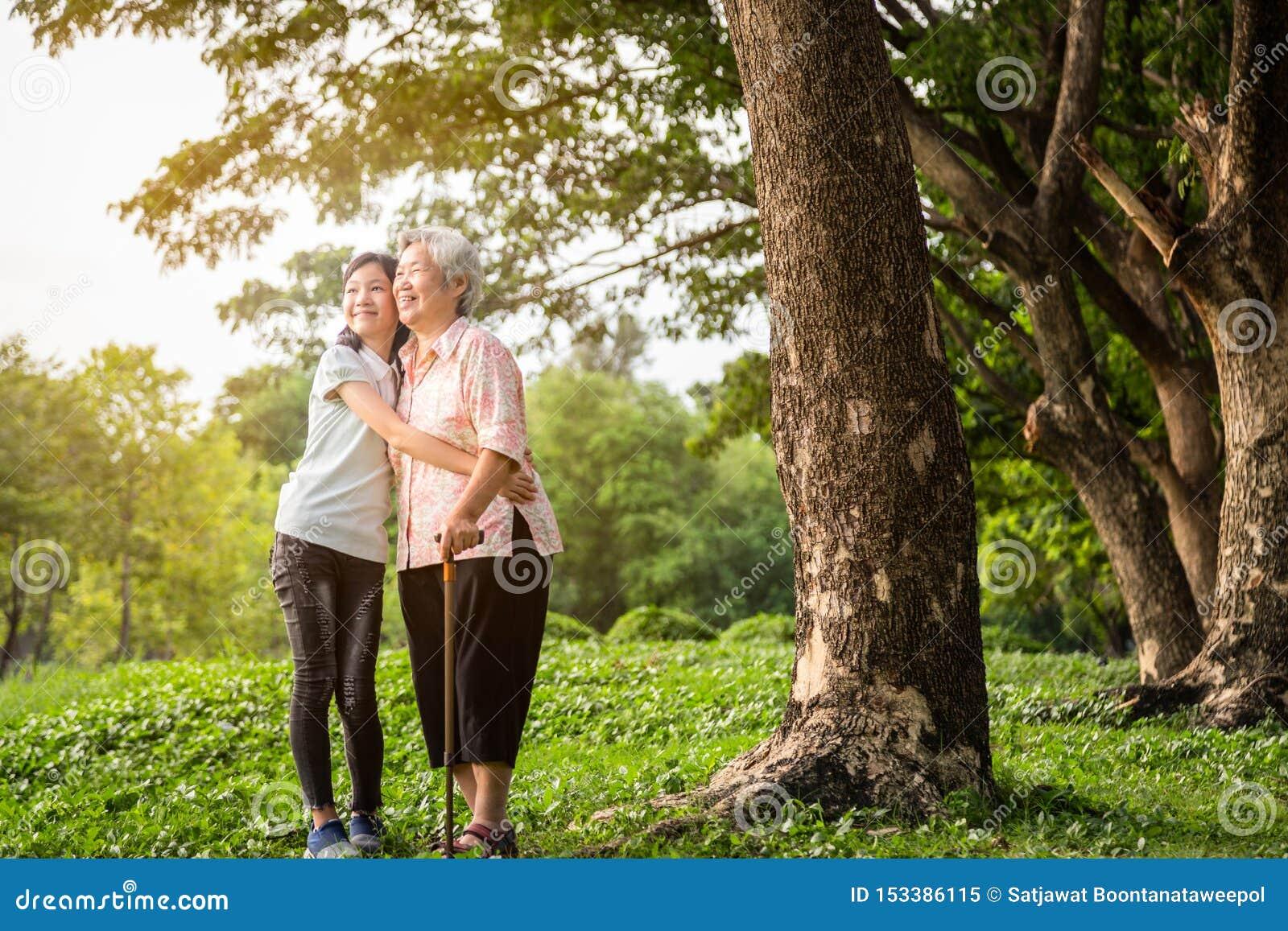 Glückliche asiatische kleines Kindermädchenunterstützung, ältere Großmutter umarmend, lächelnde Enkelin Park im im Freien, ältere