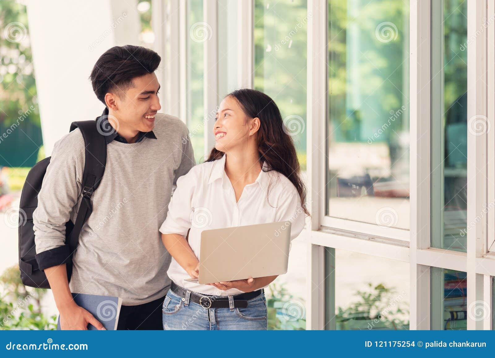 Glückliche Asiatspaarstudenten oder -kollegen benutzen Laptop-Computer a