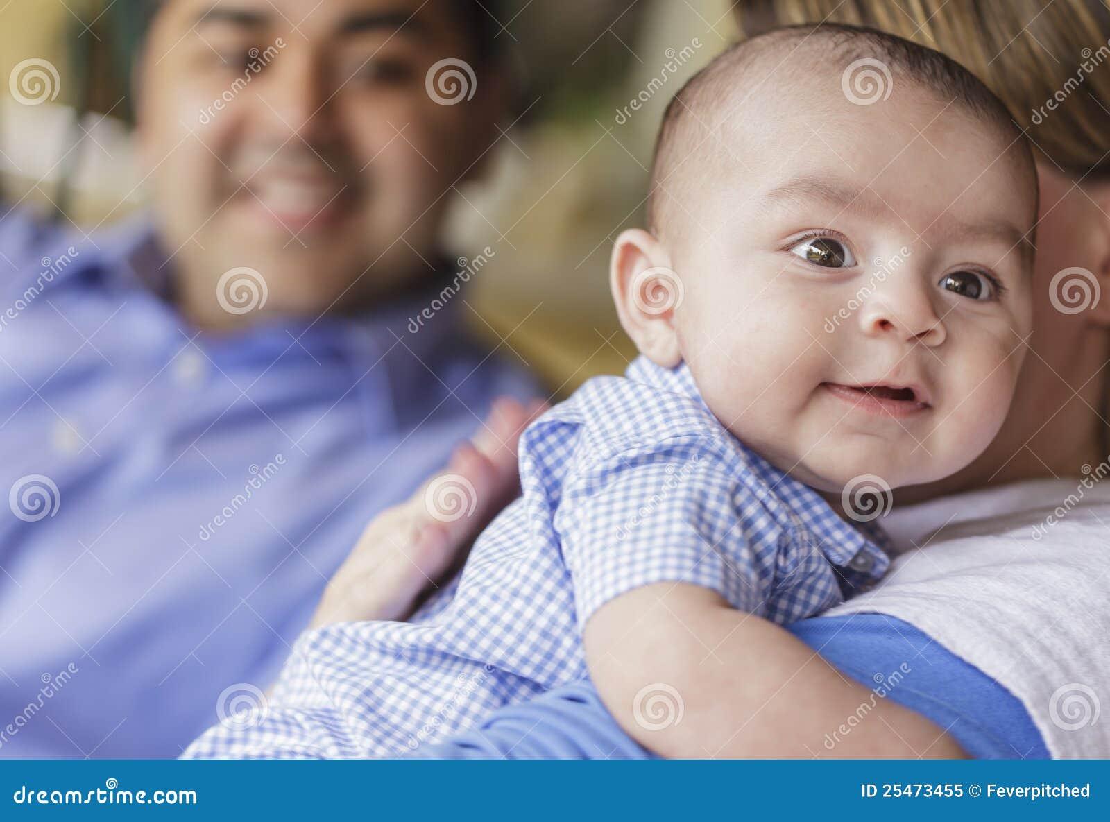 Glückliche attraktive Mischrasse-Paare, die ihren Sohn rülpsen
