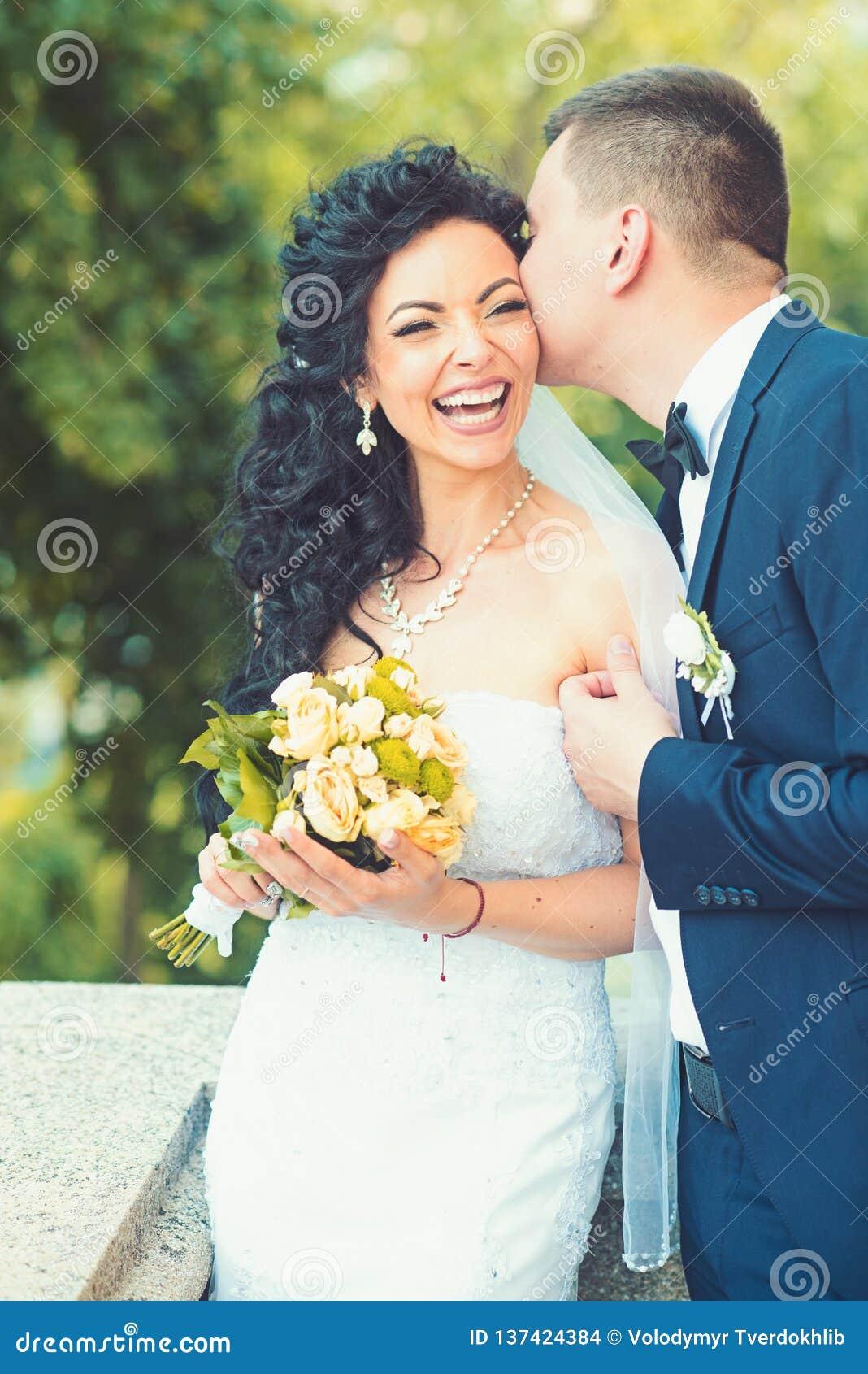 Glückliche Braut des Bräutigamkusses mit Blumenstrauß Frauen- und Mannlächeln am Hochzeitstag Hochzeitspaare in der Liebe Jungver