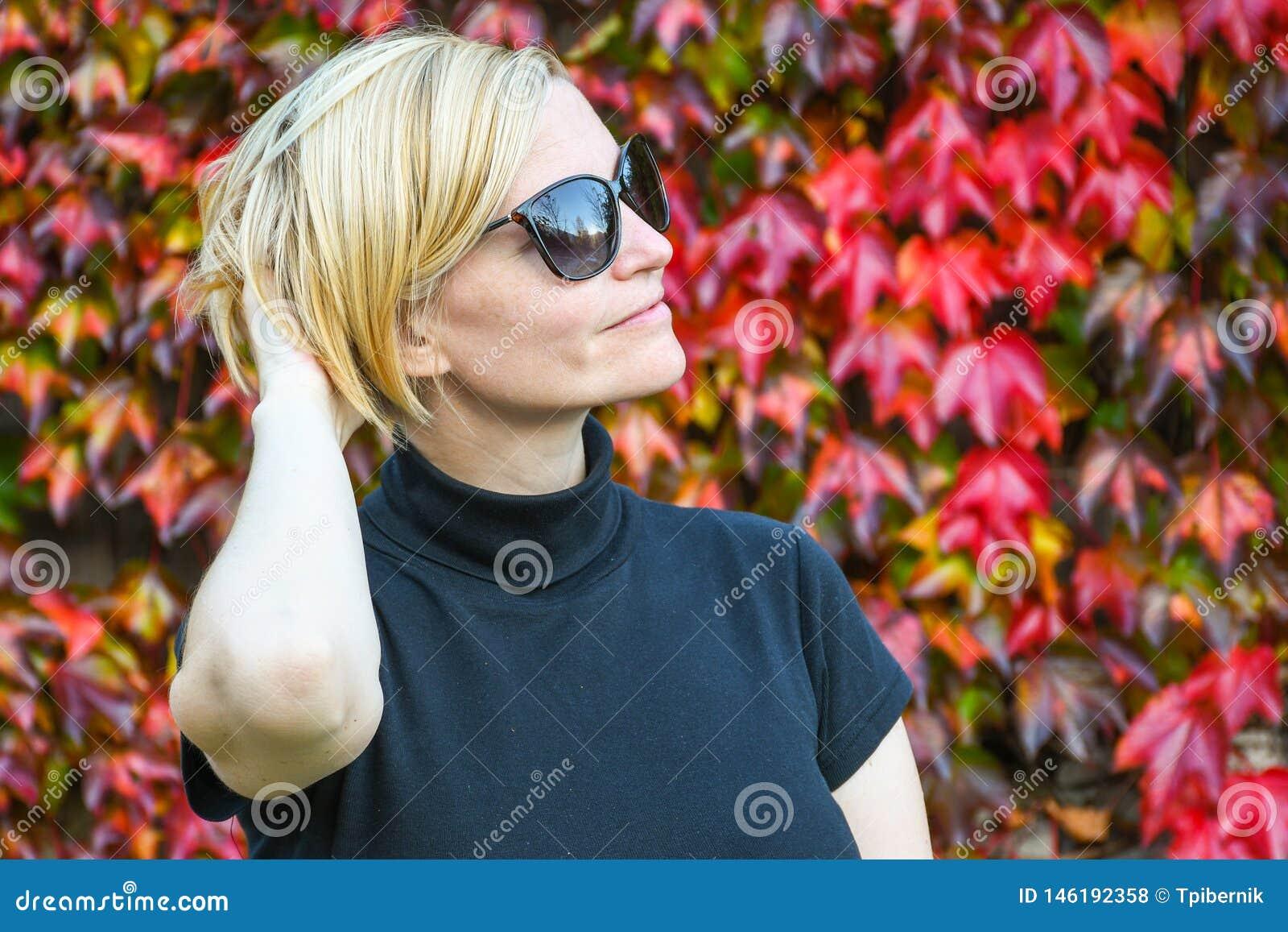 Glückliche entspannte Frau mit schwarzer Sonnenbrille und dem Hemd, die ihren Arm auf der Rückseite ihres Kopfes hält