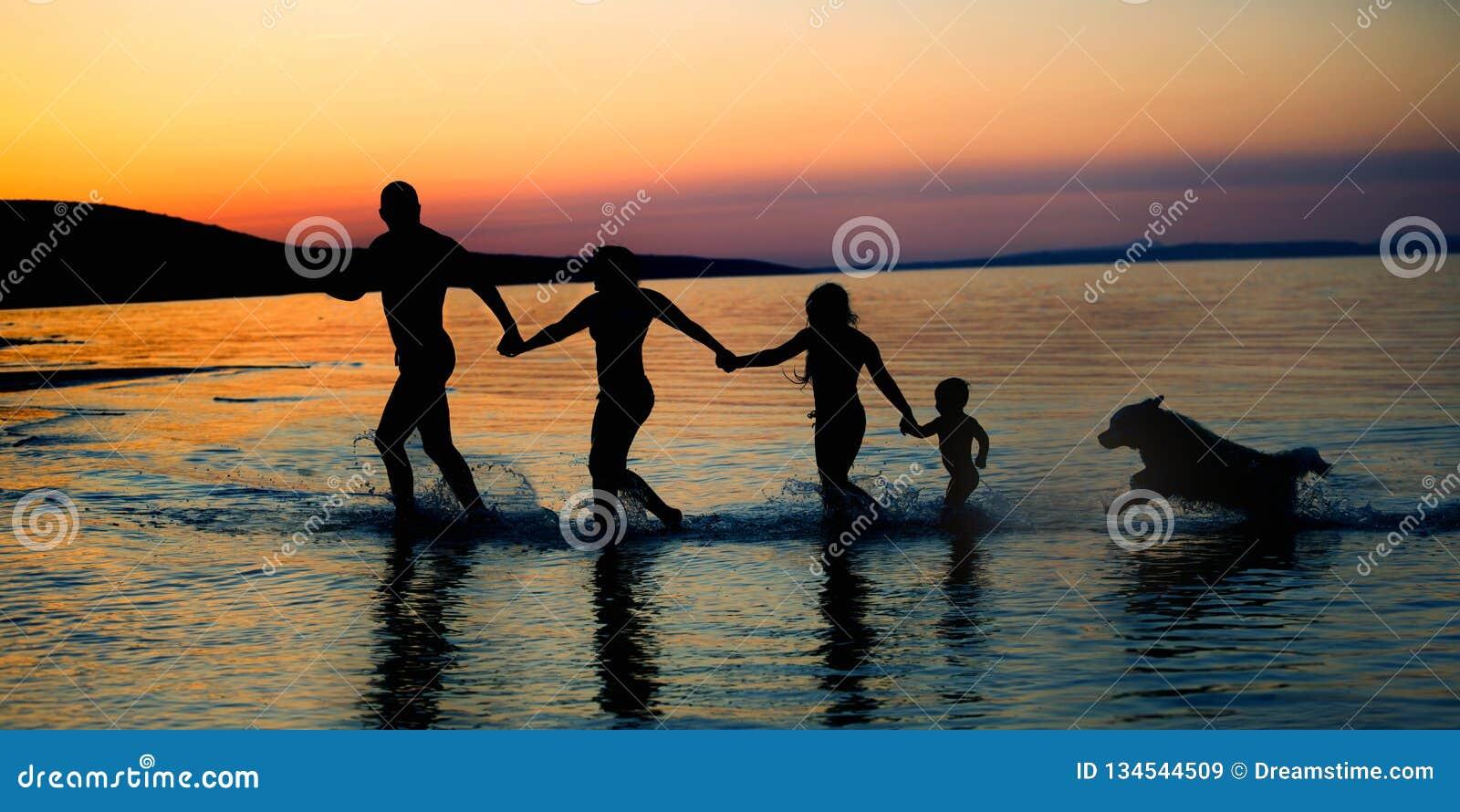 Glückliche Familie auf Strandsonnenuntergang