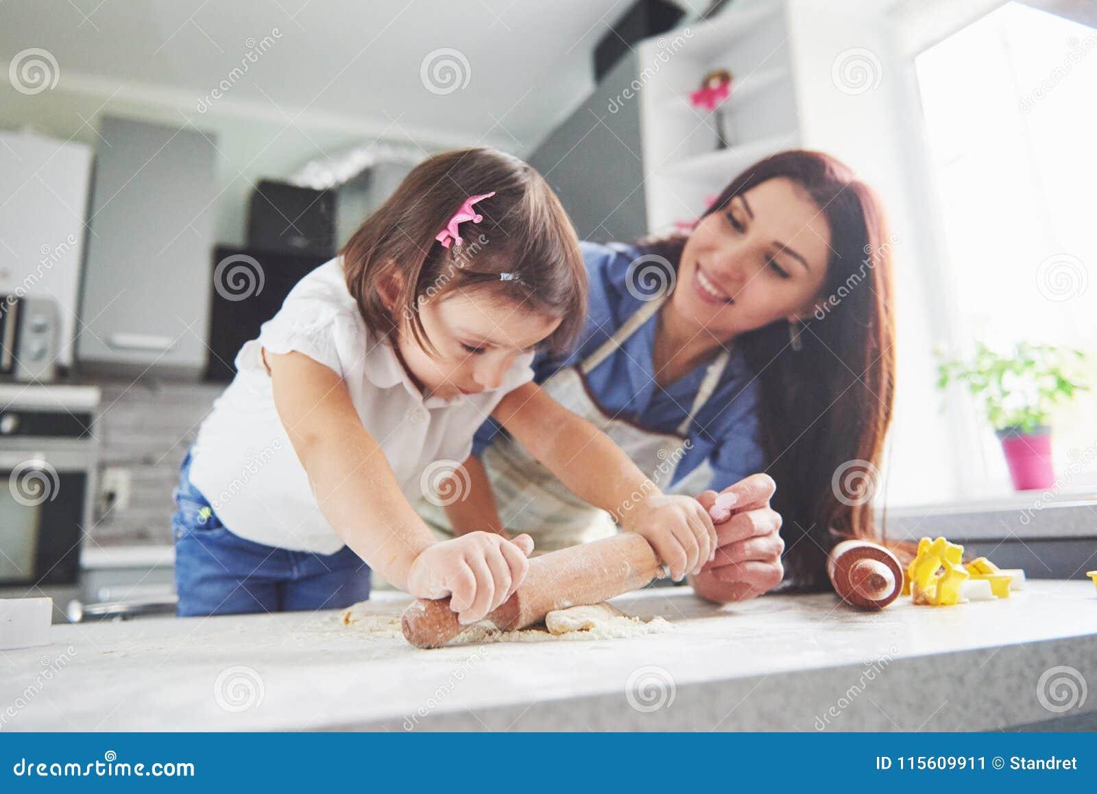 Glückliche Familie in der Küche Feiertagslebensmittelkonzept Die Mutter und Tochter, die den Teig zubereiten, backen Plätzchen Gl